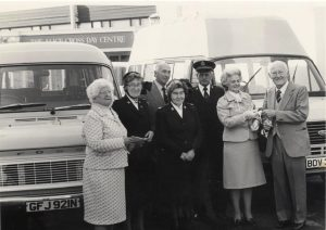Group standing in front of 2 minibuses