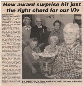 Newspaper article photo of Viv Wilson receiving the trophy with supporters behind